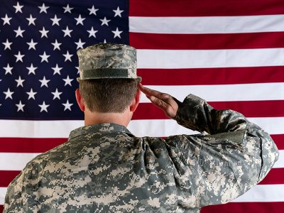 soldier saluting in front of flag