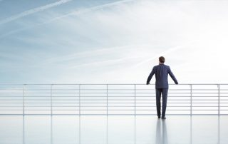 Businessman standing on a roof and looking at sky